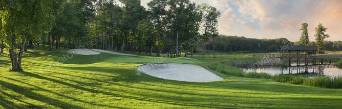 Panorama of a golf green and bridge in late afternoon sunlight