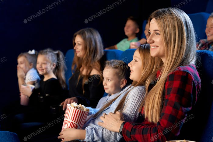 Mother watching movie with daughter in cinema
