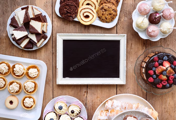 Picture frame and cake, cookies, tarts, cupcakes. Copy space.