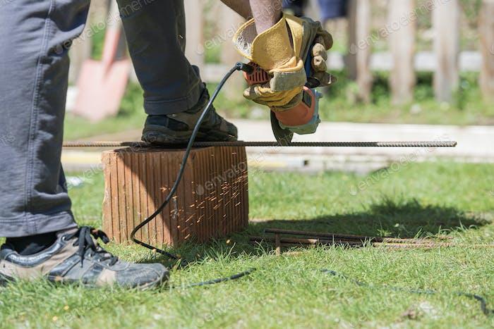 Man cutting steel rod, working on a back yard project