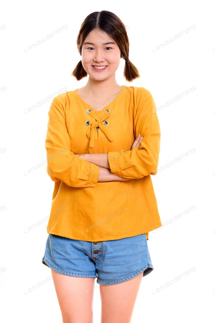 Studio shot of young happy Asian woman smiling while standing wi