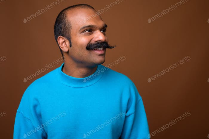 Face of happy Indian man with mustache wearing blue sweater