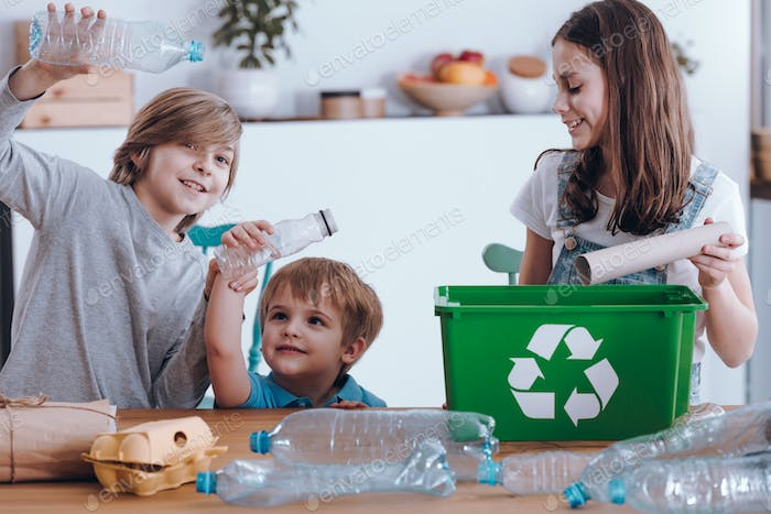 Smiling children segregating plastic bottles