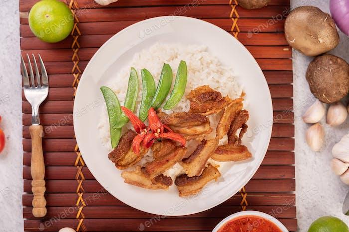 Schweinebauch gebraten auf gedämpftem Reis auf einem Teller.