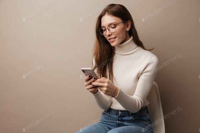 Foto de encantadora mujer sonriente usando el teléfono celular y sentado en la silla