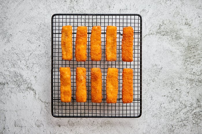 Rows of golden fried fresh fish fingers fillets