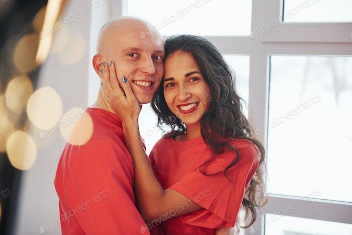 Fröhliches Paar steht am Fenster, lächelt und blickt in die Kamera