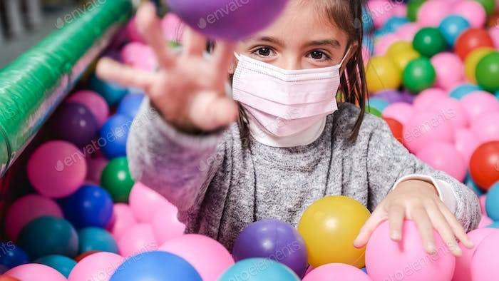 happy 5 year old girl with mask in a ball pool throwing balls to camera