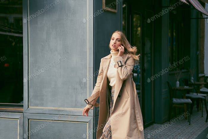 Beautiful blond girl in stylish trench coat talking on cellphone on street