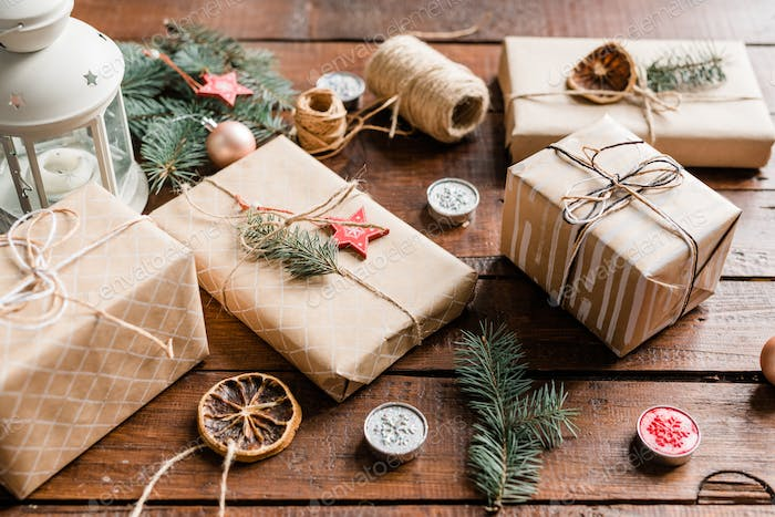 Wrapped giftboxes surrounded by conifer, candles, decorations and threads