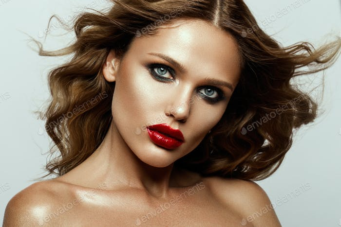 Beautiful face of a fashion model with blue eyes.Curly hair. Red lips