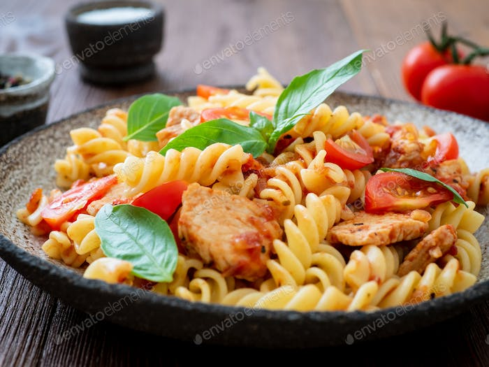 fusilli pasta with tomato sauce, chicken fillet with basil leaves