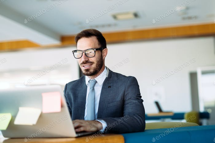 Young handsome architect working on laptop in office