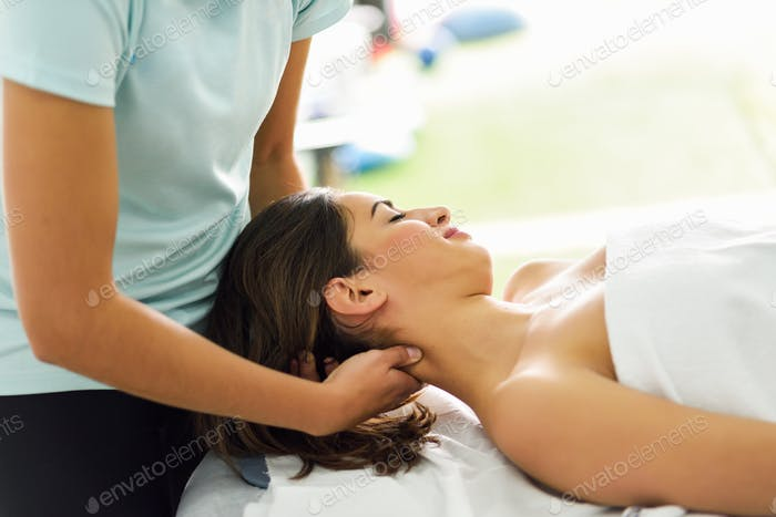 Young smiling woman receiving a head massage in a spa center.