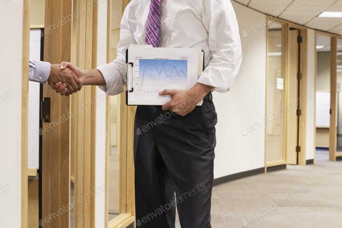 Eine Nahaufnahme von zwei Geschäftsleuten, die in einem Bürobereich die Hände schütteln.