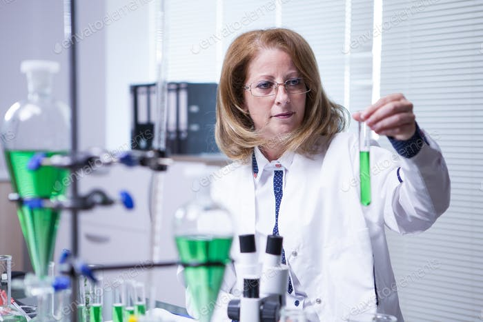 Female scientist wearing a white coat in a research lab