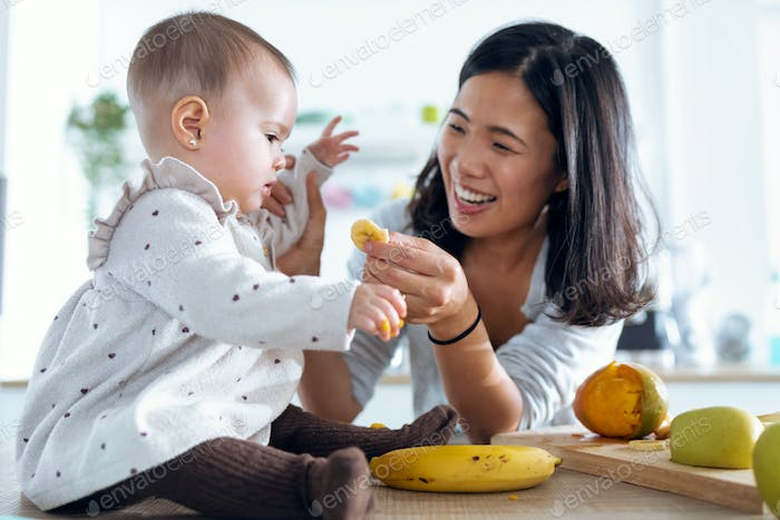 Happy young mother feeding her cute baby girl with a banana in the kitchen at home.