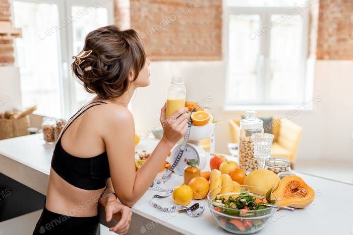 Sports woman with healthy food on the kitchen