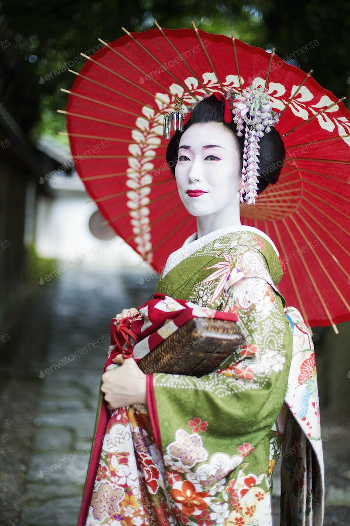 A geisha in traditional costume with umbrella