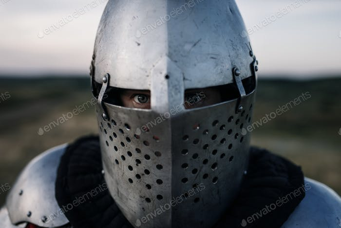Medieval knight in armor and helmet closeup view