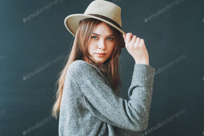 Young beautiful long brown-haired hair girl in felt hat and grey knitted sweater