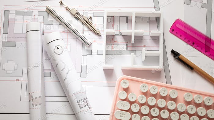 Construction concept. Residential building blueprint drawings and a pink computer keyboard
