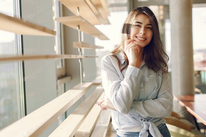 Chica sonriente en una camisa azul de pie cerca de la ventana y posando