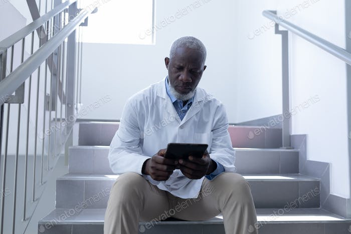 Senior african american male doctor using tablet sitting on stairs in hospital