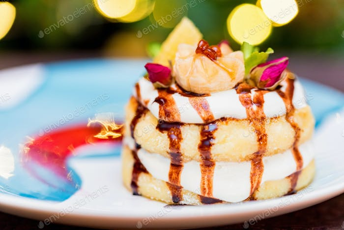 Cottage cheese pancakes or syrniki with cream, fruit jam and flower decoration