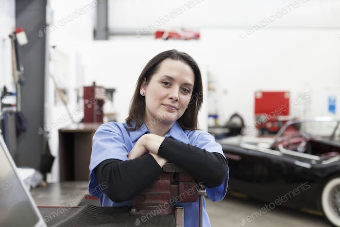A portrait of a caucasian female mechanic in a car repair shop.