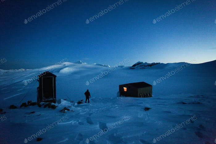 A skier walking from a hut to use the outhouse restroom, Wapta Traverse.
