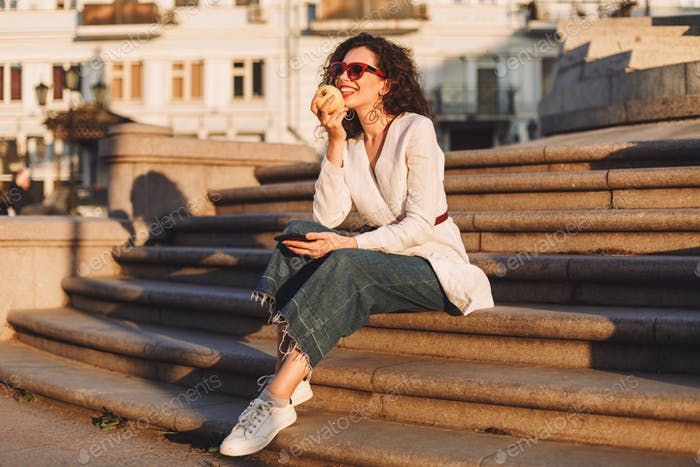 Beautiful stylish smiling lady in sunglasses sitting on city stairs with cellphone and apple