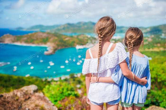 Adorable little kids enjoying the view of picturesque English Harbour at Antigua in caribbean sea
