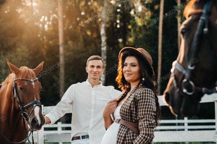 ein schwangere Mädchen in einem Hut und ihr Mann in weißer Kleidung stehen neben den Pferden in der Nähe des Pferdes