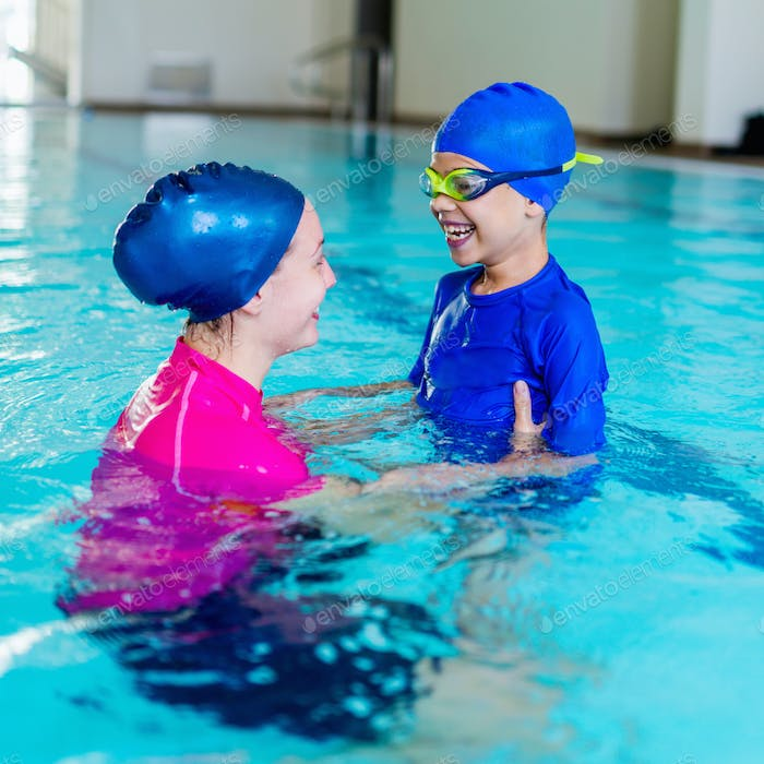 Swimming school. Cute little boy having fun with swimming instru