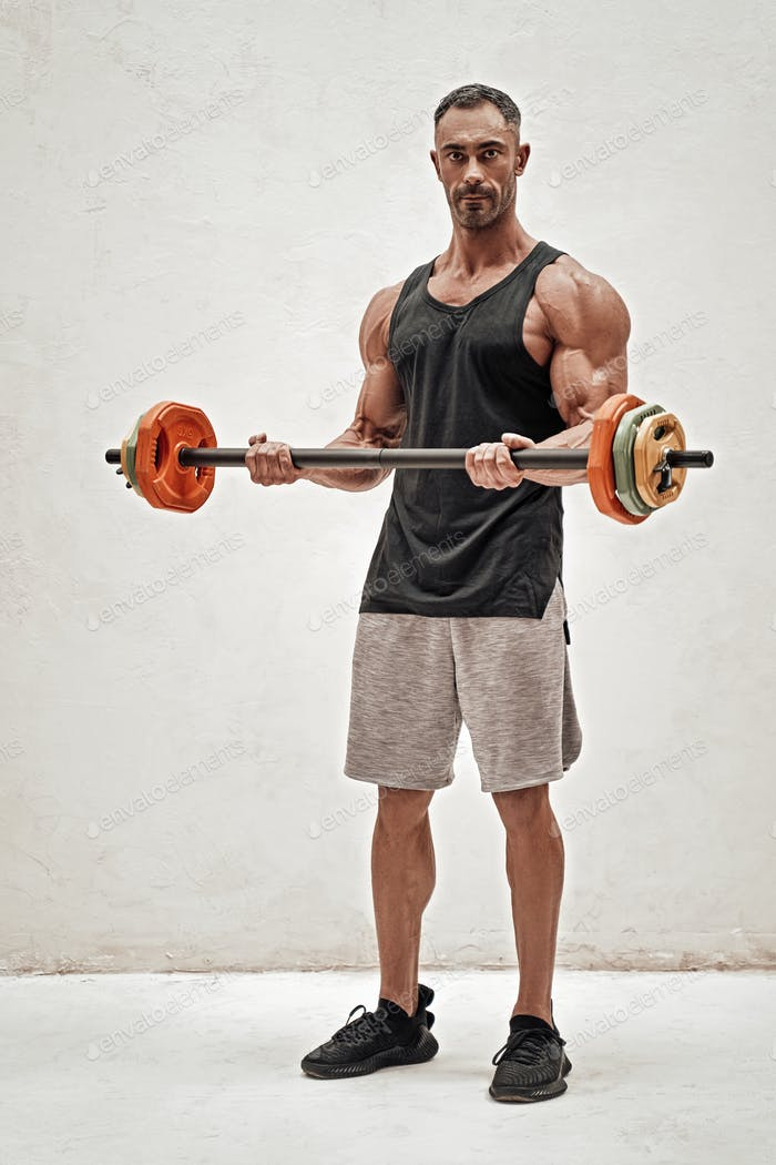 Full height portrait of a sportsman, flexing with a barbell in a bright studio