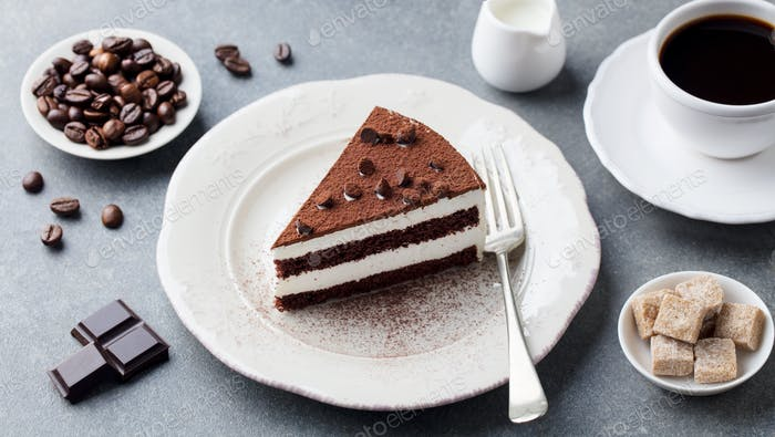 Tiramisu Cake with Chocolate Decotaion on a Plate With Cup of Coffee. Grey Stone Background.