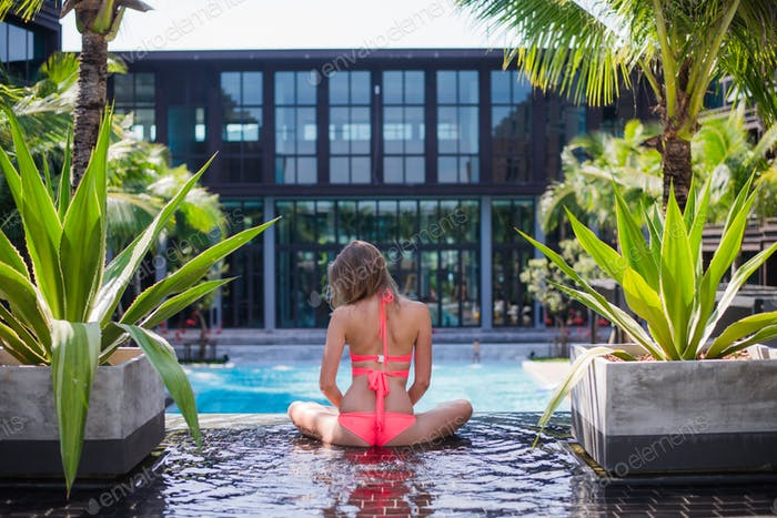 Serene meditating woman relaxing at luxury travel holiday vacation resort. Happy blissful young