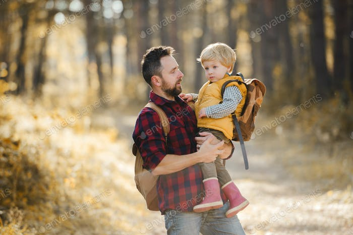 A mature father holding a toddler son in an autumn forest, talking.