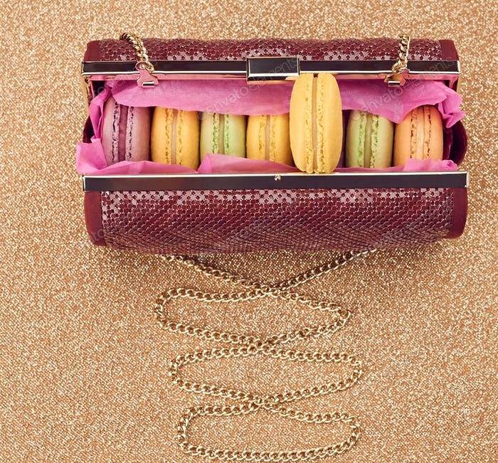 Macarons in shiny fashion handbag on gold.Vintage