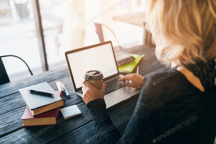 mujer joven que trabaja en el ordenador portátil en la oficina de co-working