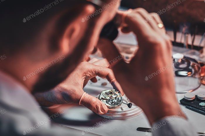 Reife Uhrmeister repariert alte Uhr für einen Kunden in seiner beschäftigten Reparaturwerkstatt