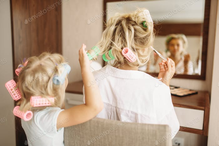 Child makes a funny hairstyle to her mother