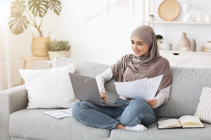 Work From Home Concept. Smiling Muslim Woman Busy With Laptop And Papers