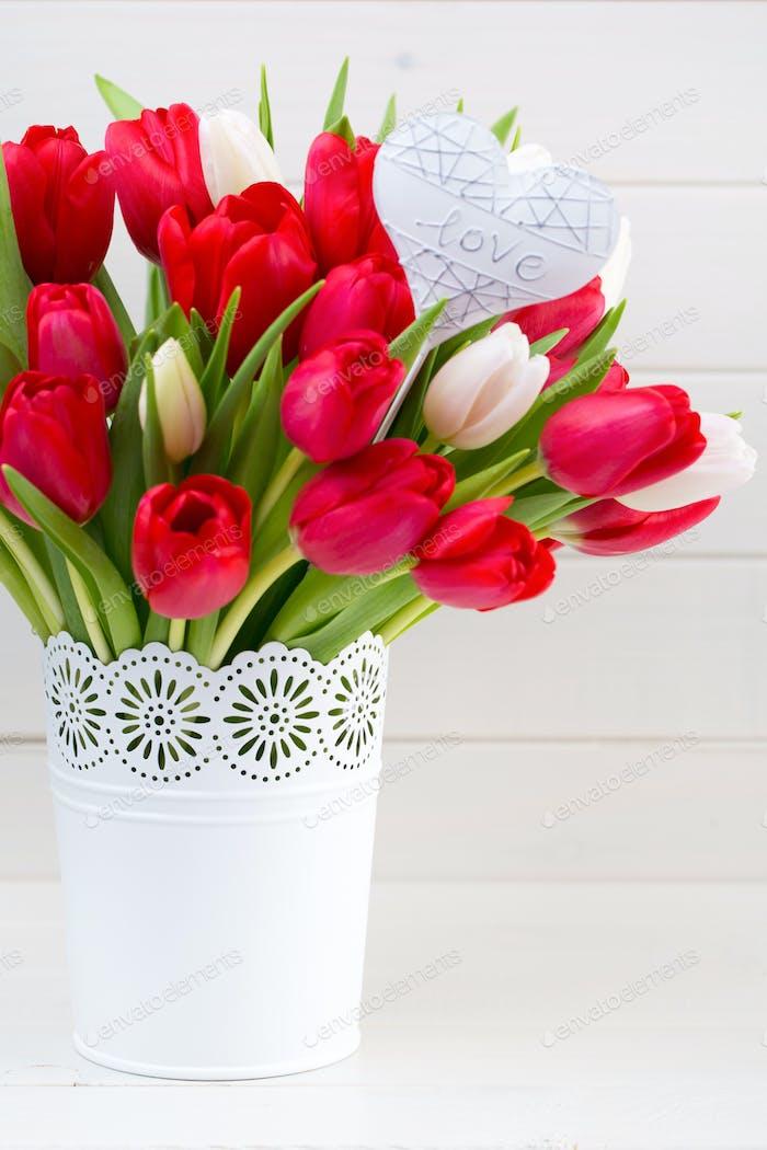 Frische rote Tulpenblüten Blumenstrauß auf Regal vor Holzwand.
