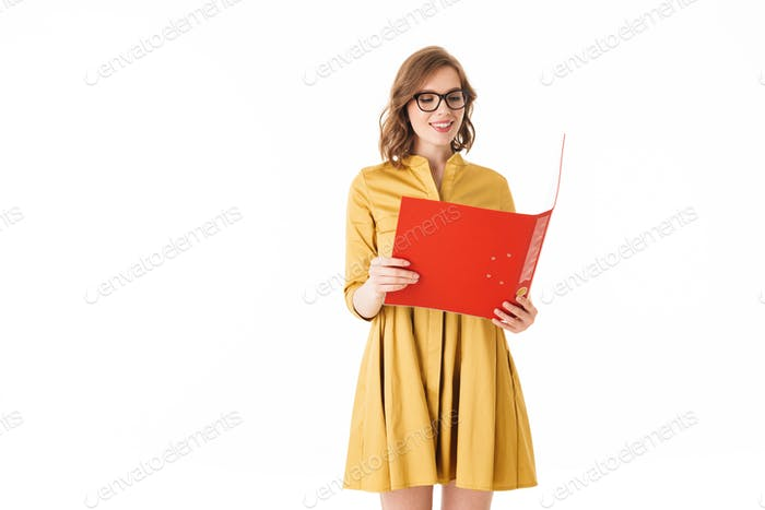 Pretty smiling lady in eyeglasses and yellow dress standing with red open folder in hand