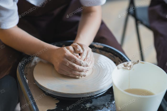 Female potter makes a pot on the pottery wheel close-up