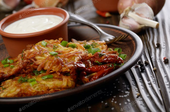 Homemade tasty potato pancakes in clay dish with sun-dried tomat