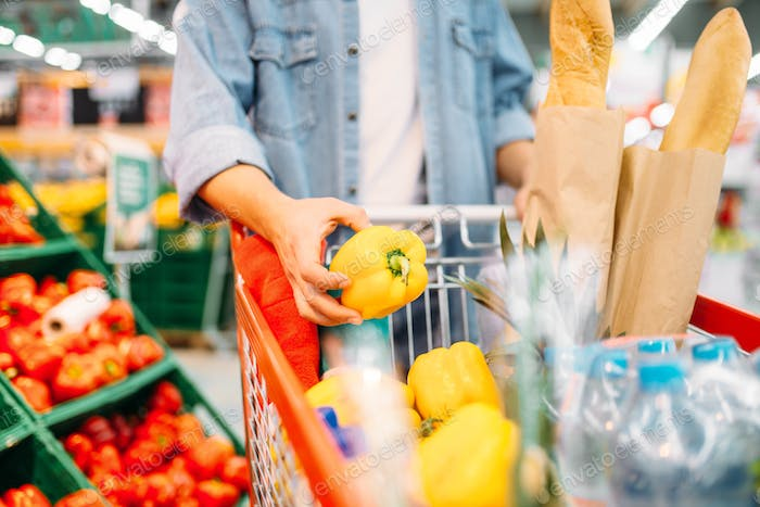 Male person puts yellow pepper in the cart
