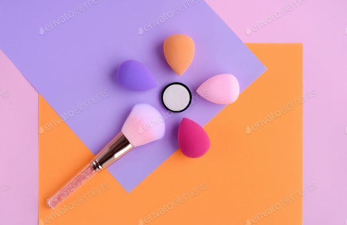 Makeup brush and sponges oncolor background, with empty space for text.